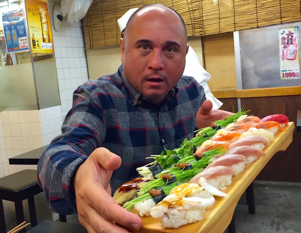 Lanai Tabura holding a plate of sushi